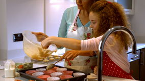 Mother and daughter are cooking cupcakes together. In the kitchen stock video footage