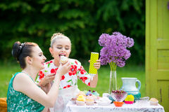 Mother and daughter cooking cupcakes. Young mother and her daughter cooking cupcakes together in the backyard royalty free stock photo
