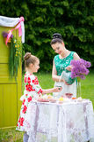 Mother and daughter cooking cupcakes. Young mother and her daughter cooking cupcakes together in the backyard stock photo