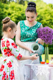 Mother and daughter cooking cupcakes. Young mother and her daughter cooking cupcakes together in the backyard stock images