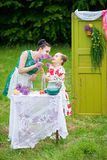 Mother and daughter cooking cupcakes. Young mother and her daughter cooking cupcakes together in the backyard Stock Photography