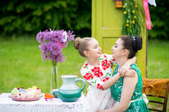 Mother and daughter cooking cupcakes. Young mother and her daughter cooking cupcakes together in the backyard stock photos