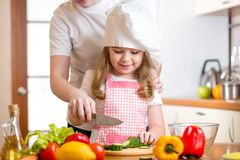 Mother and daughter cooking and cutting vegetables Stock Images