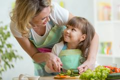 Mother and daughter cooking and cutting vegetables Stock Photo