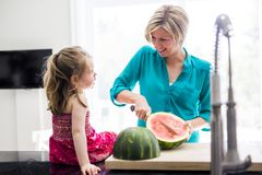 Mother and daughter cut watermelon in kitchen Royalty Free Stock Photos