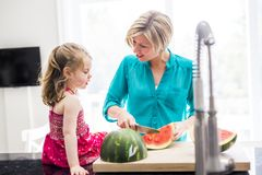 Mother and daughter cut watermelon in kitchen Royalty Free Stock Photo