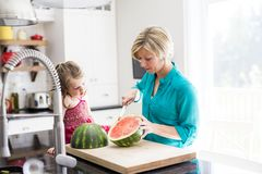 Mother and daughter cut watermelon in kitchen Stock Photo