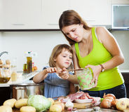 Mother with daughter cooking with groats Royalty Free Stock Photos