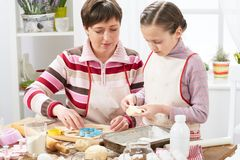 Mother and daughter cooking at home, making the dough for buns Stock Photography