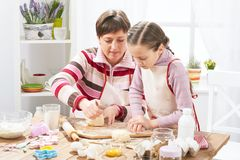 Mother and daughter cooking at home, making the dough for buns Royalty Free Stock Photos