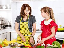 Mother and daughter cooking at kitchen. Royalty Free Stock Images