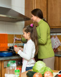 Mother with daughter cooking at kitchen Royalty Free Stock Photo