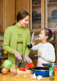 Mother with daughter cooking at kitchen Stock Photos