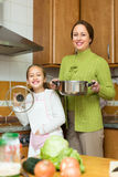 Mother with daughter cooking at kitchen Stock Images