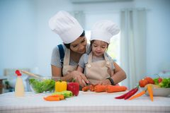 Mother and daughter cooking togather for making salad. And prepare vegetable in kitchen room Stock Image