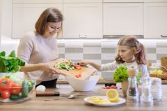 Mother and daughter cooking together in kitchen vegetable salad, parent and child are talking smiling stock image