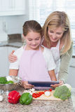 Mother and daughter cooking together with tablet pc Stock Photography