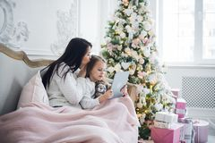 Mother With Daughter On Couch Using Tablet Computer Happy Smiling Young Family Near Decorated New Year Christmas Tree. Small Girl And Woman royalty free stock images