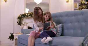 Mother With Daughter On Couch Using Tablet Computer Happy Smiling Young Family Near Decorated New Year Christmas Tree. Small Girl And Woman stock video footage