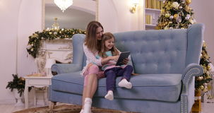 Mother With Daughter On Couch Using Tablet Computer Happy Smiling Young Family Near Decorated New Year Christmas Tree. Small Girl And Woman stock footage