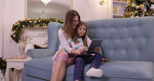 Mother With Daughter On Couch Using Tablet Computer Happy Smiling Young Family Near Decorated New Year Christmas Tree. Small Girl And Woman stock video