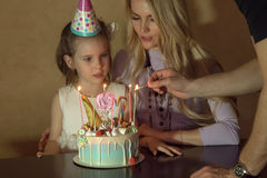 Mother and daughter countIng candles on a birthday cake. little girl in a festive hat at a children& x27;s party Stock Photo