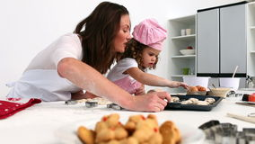 Mother and daughter counting the number of biscuits they having baked Royalty Free Stock Photos