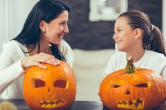 Mother with daughter creating big orange pumpkin for Halloween Royalty Free Stock Photography