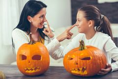 Mother with daughter creating big orange pumpkin for Halloween Stock Images