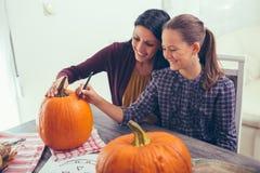 Mother with daughter creating big orange pumpkin for Halloween Stock Photo