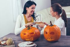 Mother with daughter creating big orange pumpkin for Halloween Royalty Free Stock Photos
