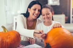 Mother with daughter creating big orange pumpkin for Halloween Stock Photos