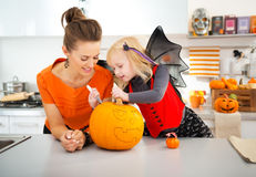 Mother with daughter creating Jack-O-Lantern on Halloween Stock Photo