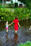 Mother with daughter crossing little river Stock Photos