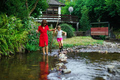 Mother with daughter crossing little river Stock Image