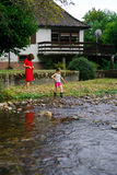 Mother with daughter crossing little river Stock Photo
