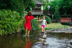 Mother with daughter crossing little river Stock Images