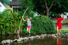 Mother with daughter crossing little river Stock Photography