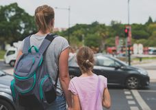 Mother and daughter crossing the road. Stock Photos