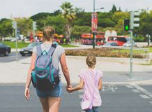 Mother and daughter crossing the road. Stock Photo