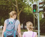 Mother and daughter crossing the road. Royalty Free Stock Images
