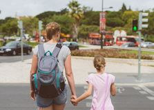 Mother and daughter crossing the road. Stock Images