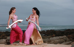 Mother and daughter crossing swords on the beach Stock Photos