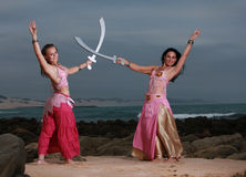 Mother and daughter crossing swords on the beach Royalty Free Stock Photo