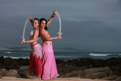 Mother and daughter crossing swords on the beach Royalty Free Stock Image