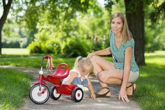 Mother With Daughter Crouching By Tricycle On Royalty Free Stock Image
