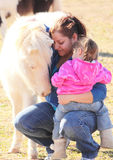 Mother and Daughter Cuddle Miniature Horse. Mother holding her daughter on her knee while petting a white miniature horse Stock Photos