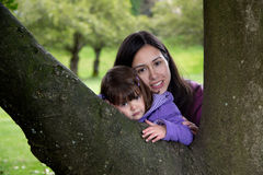 Mother and Daughter Cuddling as they Rest on a Tree. Beautiful Mother and Daughter Resting on a Tree as they Enjoy Nature Royalty Free Stock Photo