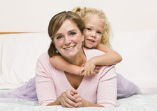 Mother and Daughter Cuddling on Bed Stock Photos