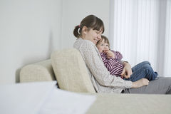 Mother And Daughter Cuddling On Sofa Stock Images